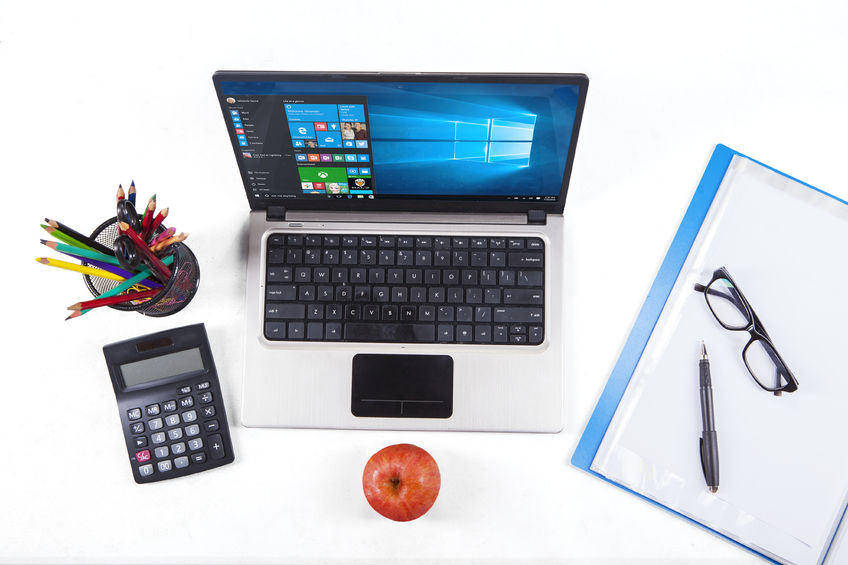 57130409 - jakarta, september 02, 2015: closup of stationery and laptop computer using the new software of windows 10
